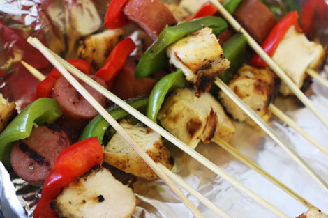 Grilled cajun chicken skewers with slices of turkey sausages and red and green bell peppers on wooden skewers in an alumninum pan.