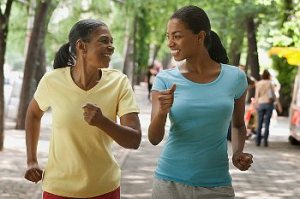 Two women, one younger and one older, power walking in the park