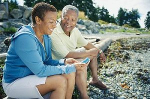 A senior couple resting after a workout with the woman using a blood sugar monitor