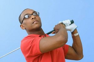 A man in a red polo shirt and wearing glasses swinging a golf club