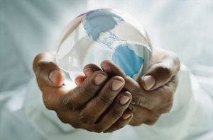 A pair of male hands holding a glass globe of the Earth