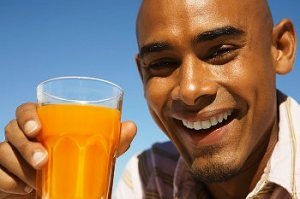 A smiling man holding a glass of orange juice