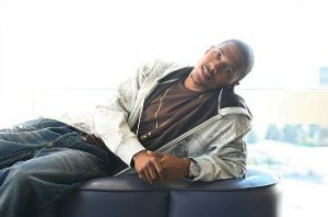 Nick Cannon reclining on a low sofa
