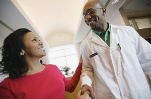 A woman shaking hands with her doctor