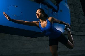 An exercising woman in blue stretching her leg