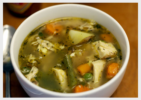 White bowl of chicken vegetable soup (w/ carrots, string beans, peas, potatoes)