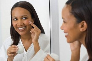 A woman applying acne treatment looking in the mirror