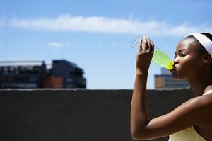 A woman drinking a yellow sports drink