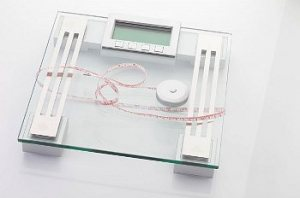 Weight loss tools, including a clear glass scale and a tape measure