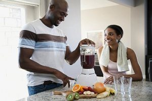 A husband and wife in their kitchen making smoothies