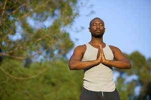 A meditating man standing outside with his hands clasped in prayer